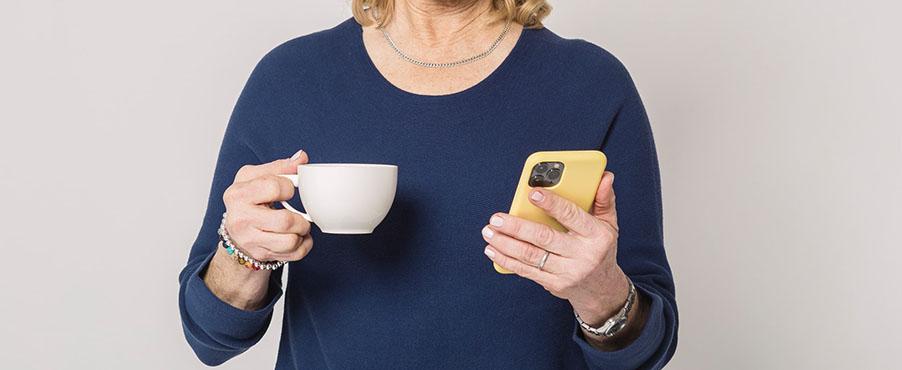 Bildanschnitt einer älteren Frau, die in der linken Hand eine Tasse und der rechten ein Smartphone hält.