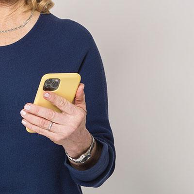 Bildanschnitt einer älteren Frau, die in der rechten Handein Smartphone hält.