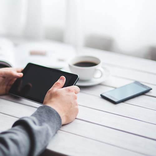 Jemand sitzt an einem Tisch und hält ein Tablet in der Hand, auf dem Tisch liegt ein Smartphone