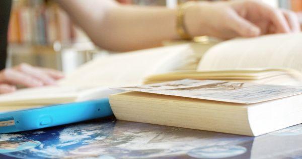 Lernende mit Bücherstapel und Tablet am Tisch