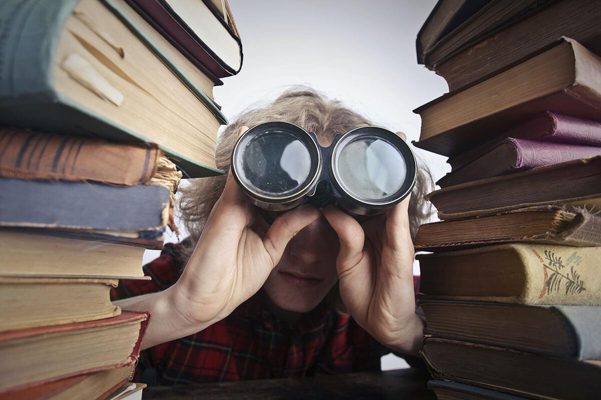 Zwischen zwei Bücherstapeln sitzt ein mensch und schaut durch ein Fernglas.