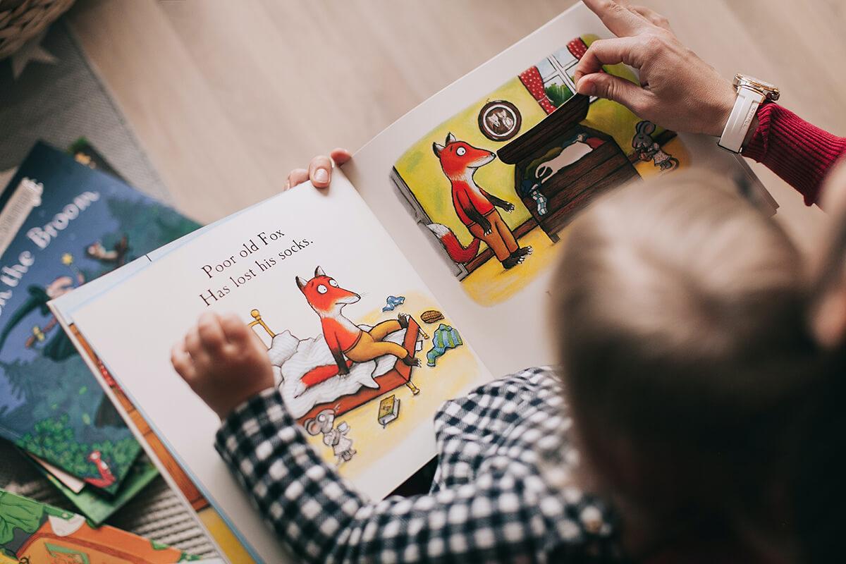 EInem Kleinkind wird aus einem Bilderbuch vorgelesen.