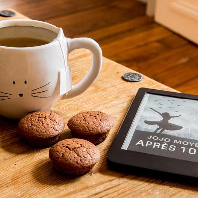 Auf einem Holztisch stehen eine Tasse Tee, 3 Cupcakes und ein E-Book-Reader.