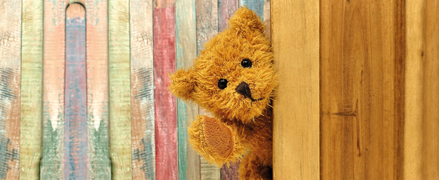Der Lesebär, ein brauner Teddy, lugt um die Ecke.