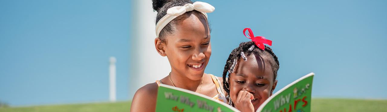 Auf einer Wiese liest ein älteres Mädchen einem jüngeren Mädchen etwas vor.
