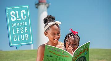 Logo des SommerLeseClubs / 2 dunkelhäutige Mädchen lesen gemeinsam ein Bilderbuch. Sie sitzen dabei auf einer Wiese, im Hintergrund erkennt man einen Leuchtturm.