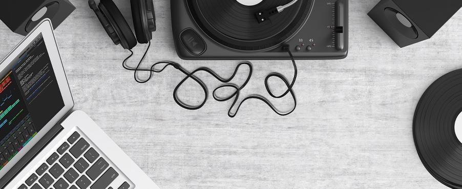 Auf einem Schreibtisch stehen ein Schallplattenspieler, an den Kopfhörer angeschlossen sind. Dort stehen auch Lautsprecherboxen und ein PC, mit dem die Schallplatte vom Plattenspieler auf den PC übertragen wird.