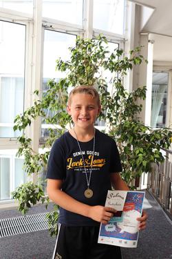 Auf dem Foto sieht man den Einzelpreisgewinner Benn Buschmann. Das Foto wurde in der Bibliothek aufgenommen, im Hintergrund steht eine große Pflanze. Der Junge hält seine Urkunde in der Hand und lächelt.