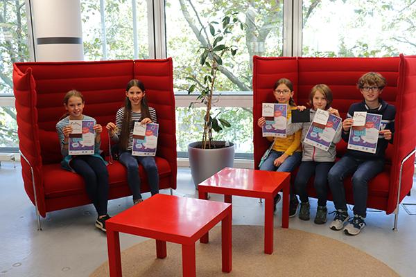 Auf zwei großen roten Sofas sitzen die glücklichen 5 Gewinner des Teampreises. Sie halten alle ihre Urkunde in der Hand.